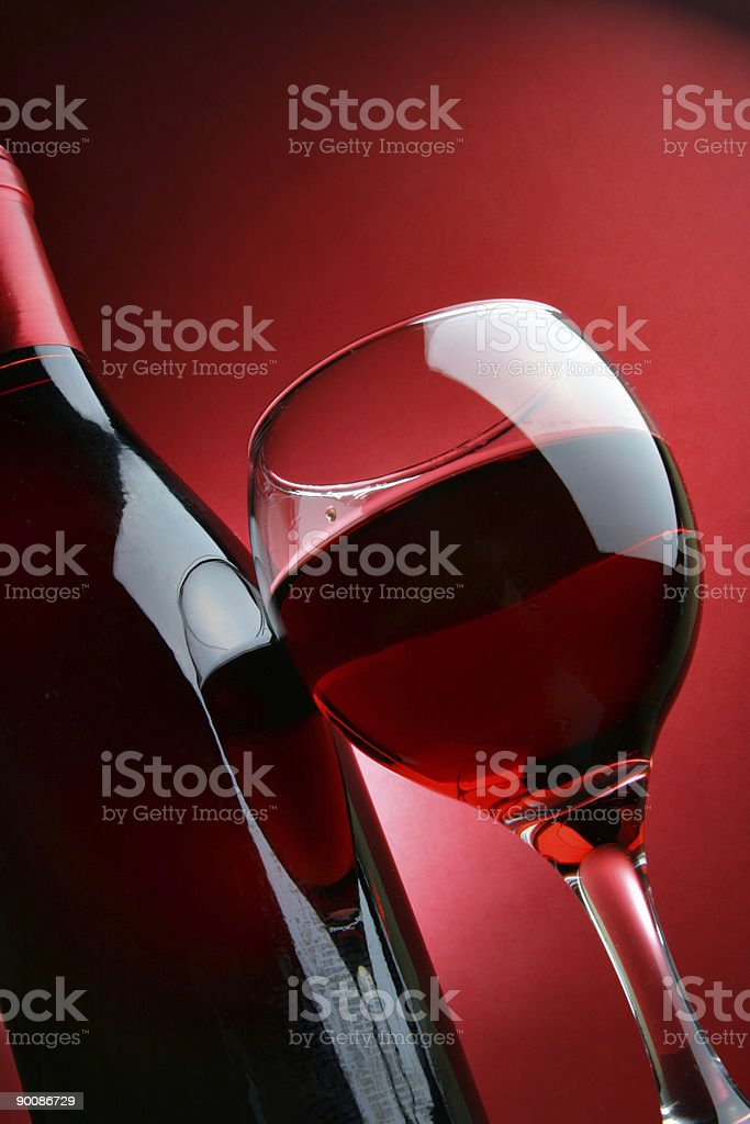 Bottle and glass full of red wine over a red backdrop royalty-free stock photo