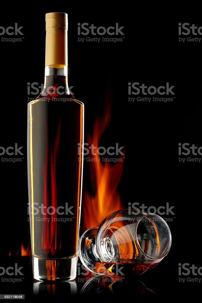 Bottle and glass of cognac over dark background with flame stock photo