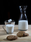 Bottle and glass of milk with cookies and a sugar cube