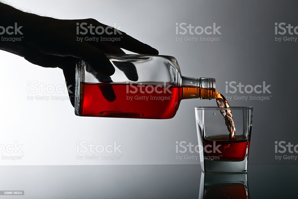 bottle and glass of whiskey on a glass table stock photo