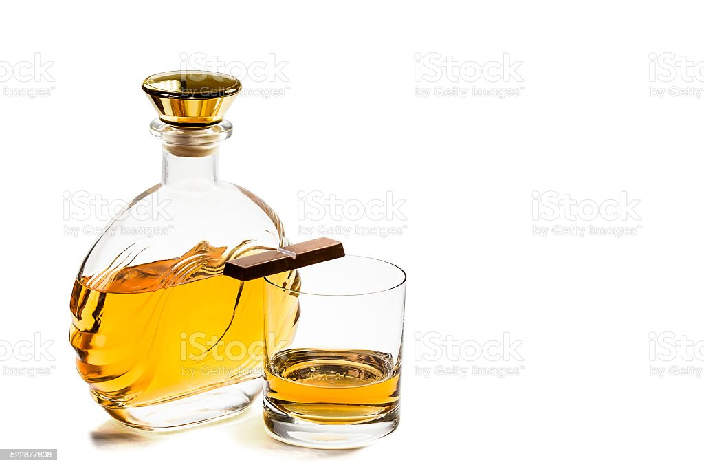 Bottle and glass whiskey with chocolate on white background stock photo