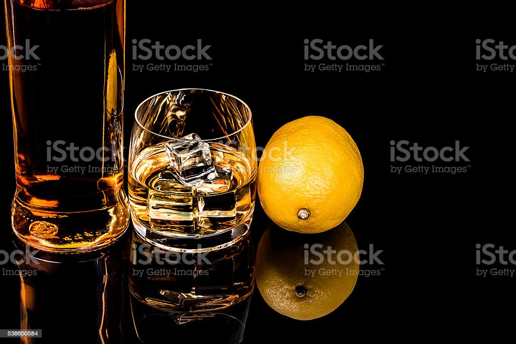 Bottle and glass whiskey with lemon on black background stock photo