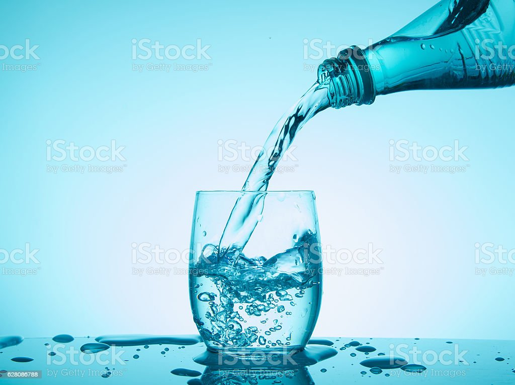 Bottle and glass with creative splashing water on blue backgroun stock photo