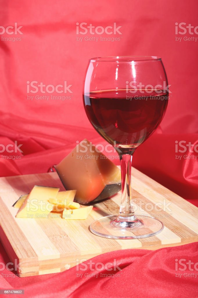 Bottle and Glass with red wine grapes and chees on wooden table. stock photo