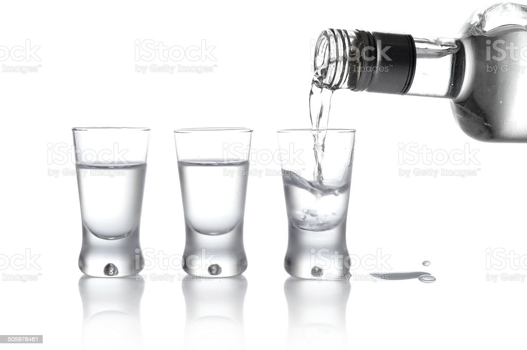 Bottle and glasses vodka poured into glass isolated on white stock photo