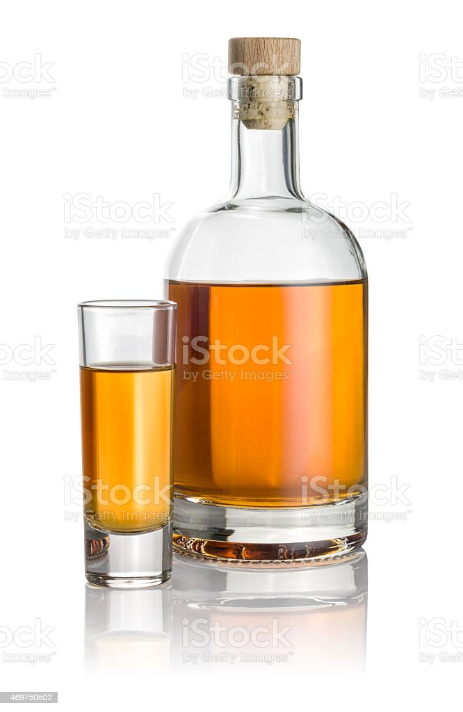 Bottle and high shot glass filled with amber liquid stock photo