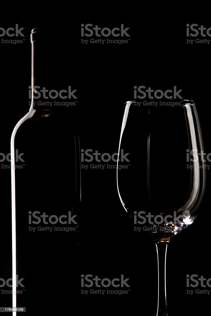 Bottle and red wine cup on dark black studio, reflection. royalty-free stock photo