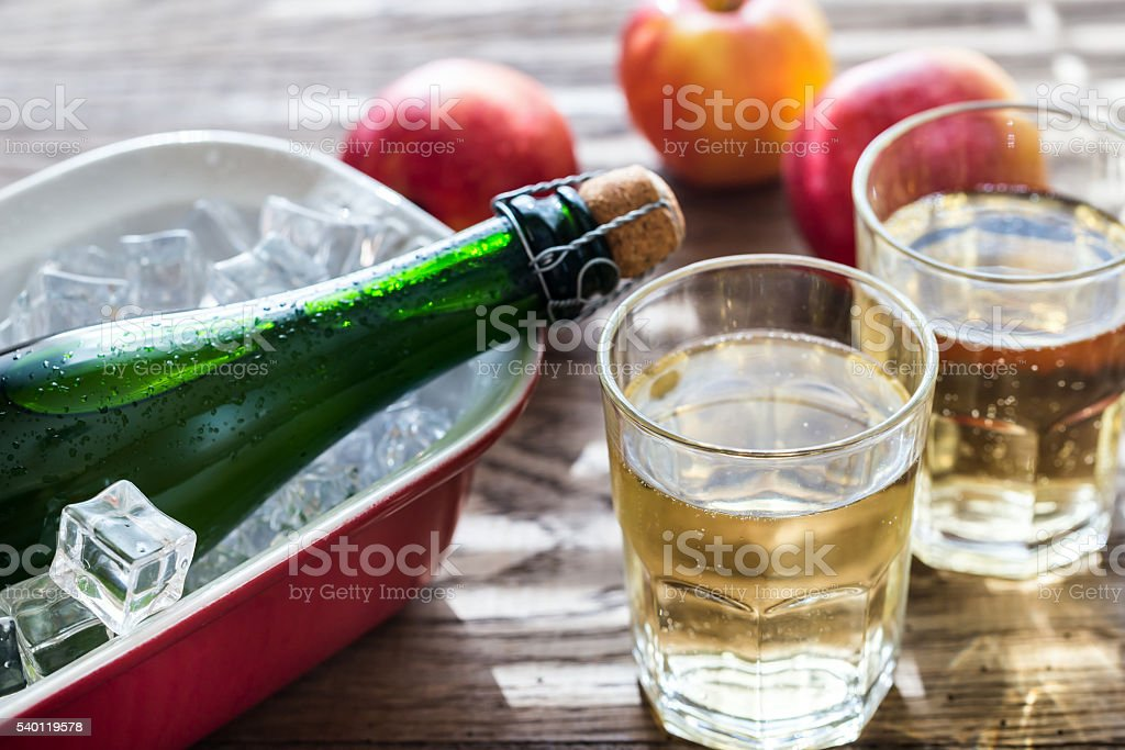 Bottle and two glasses of cider on the wooden background stock photo
