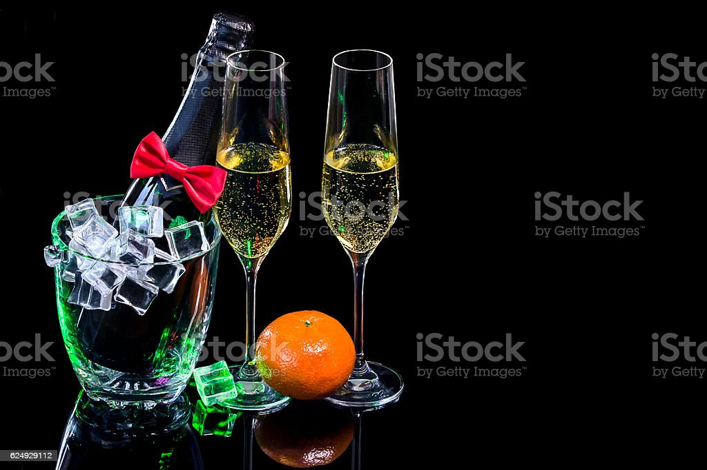 Bottle champagne in ice bucket and wineglasses with mandarin stock photo