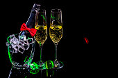 Bottle champagne in ice bucket with wineglasses and ball