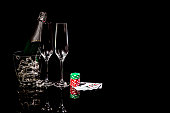 Bottle champagne in ice bucket with wineglasses and cards and chips