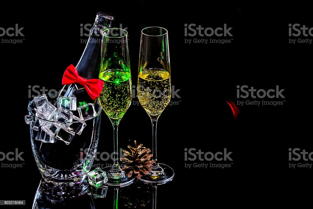 Bottle champagne in ice bucket with wineglasses and cone stock photo