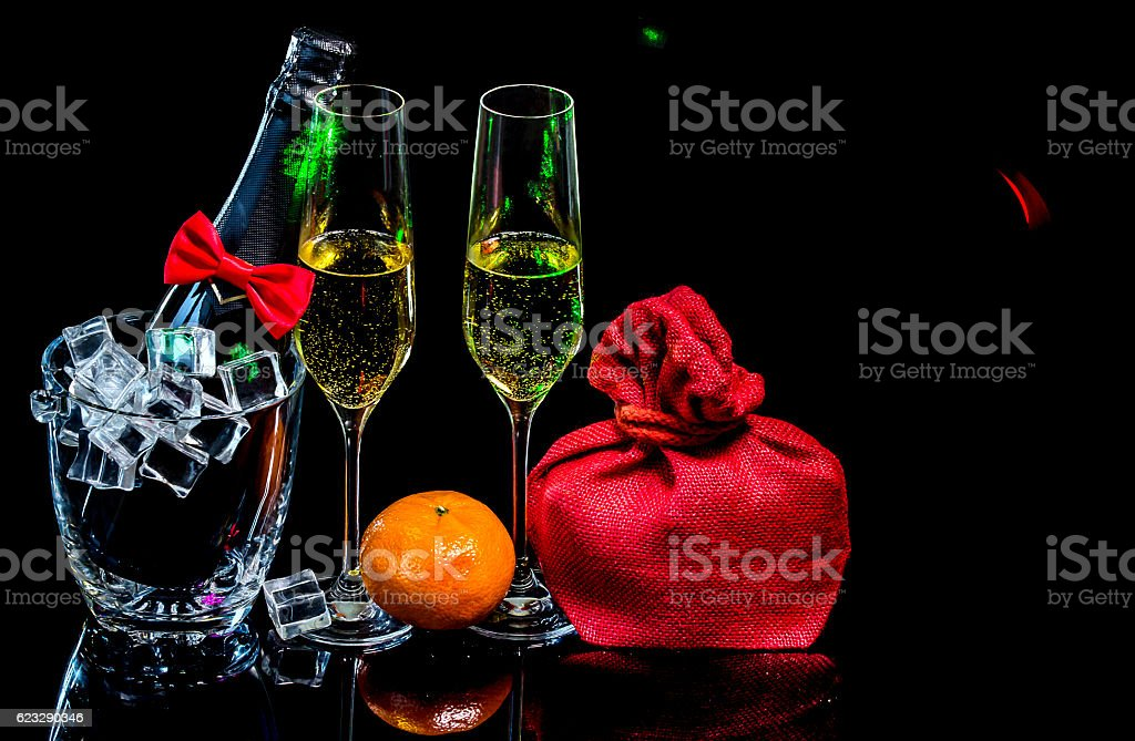 Bottle champagne in ice bucket with wineglasses and gift in bag stock photo