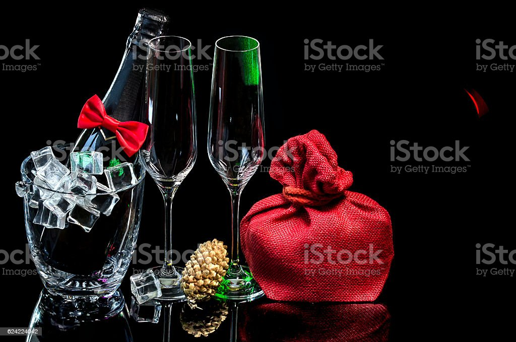 Bottle champagne in ice bucket with wineglasses and gift stock photo