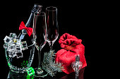 Bottle champagne in ice bucket with wineglasses and gift