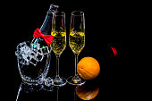Bottle champagne in ice bucket with wineglasses and orange