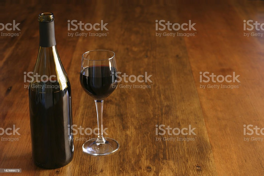 Bottle & Glass of Red Wine on Rustic Table royalty-free stock photo