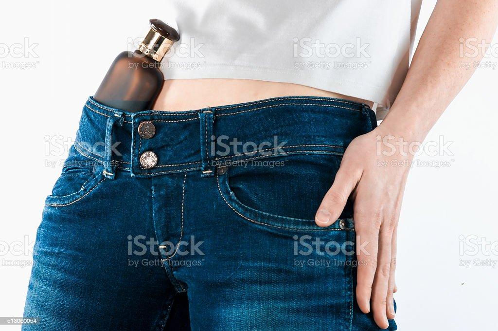 Bottle in jeans belt stock photo