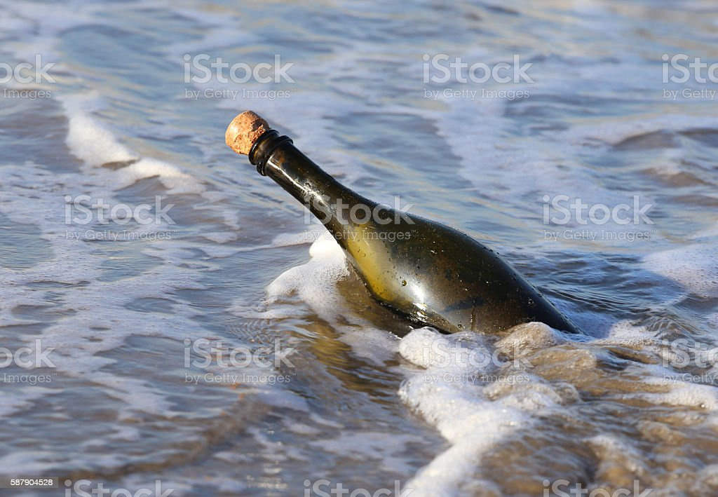 bottle in the ocean with a secret message stock photo