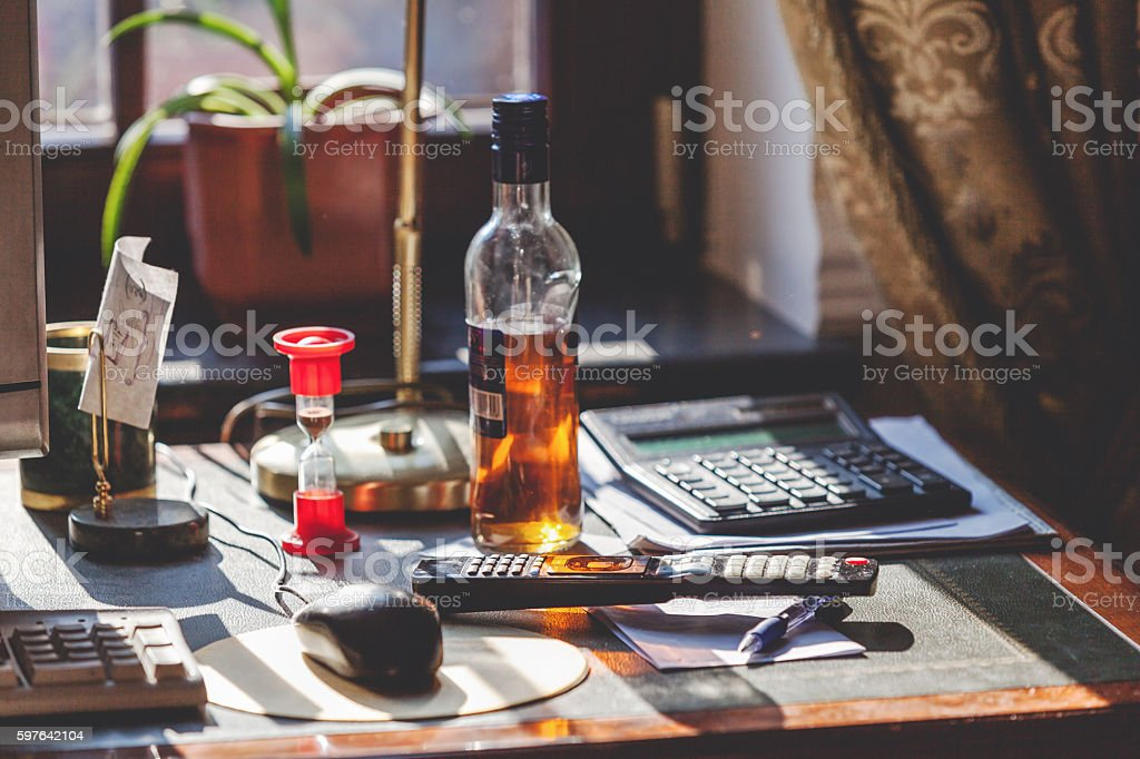 Bottle of alcohol and hourglass on your desktop stock photo