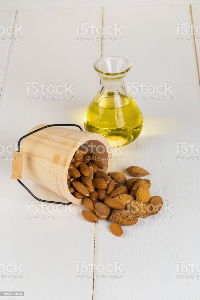 Bottle of almond oil and almonds on white wooden background. stock photo