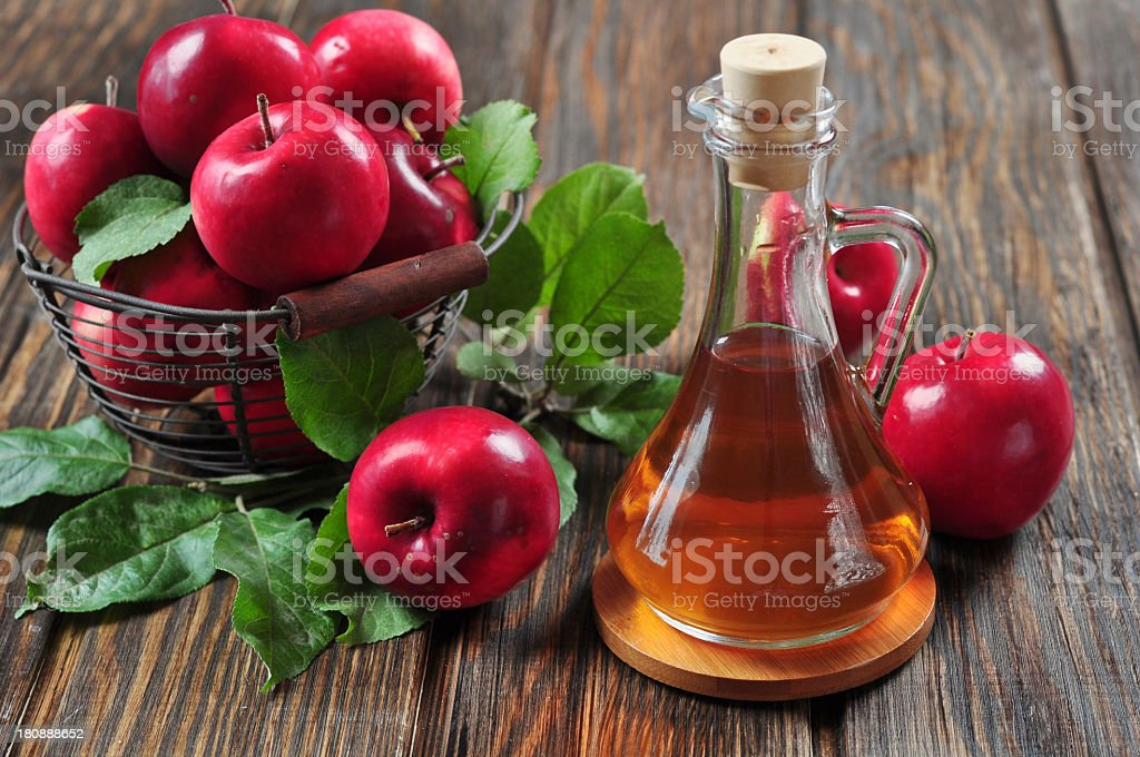 A bottle of apple cider vinegar and a bucket of apples stock photo