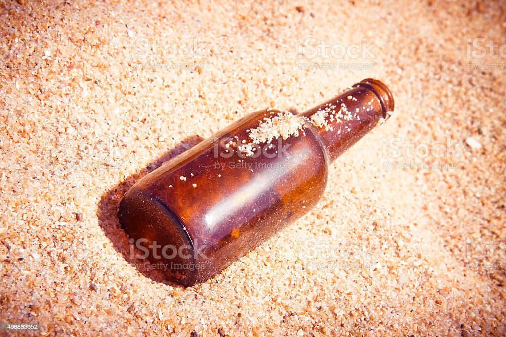 Bottle of beer glass abandoned on the beach stock photo
