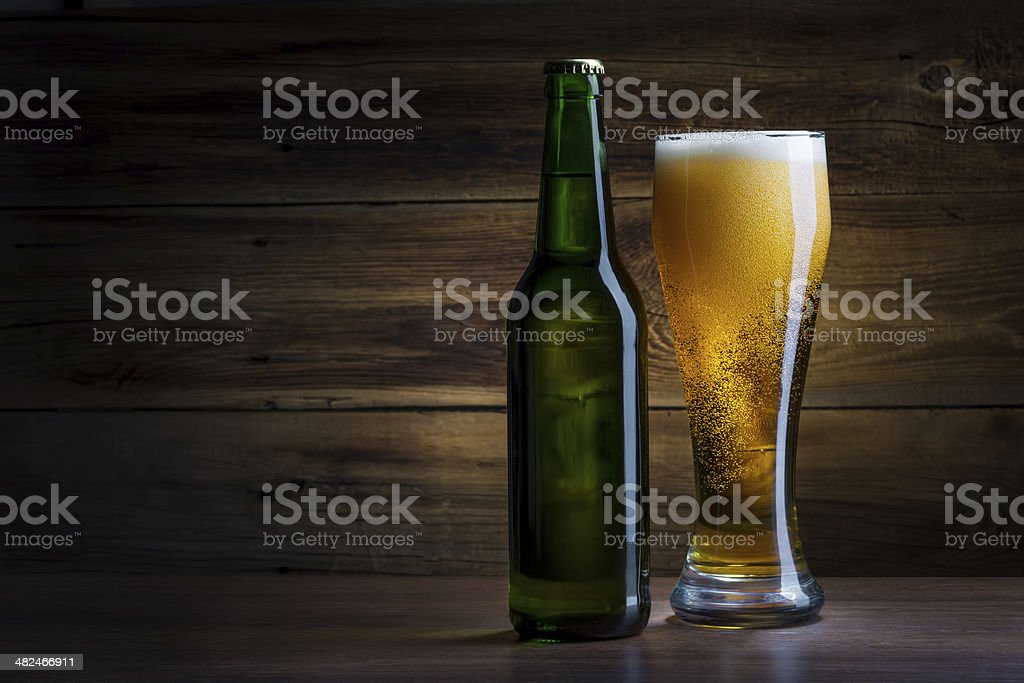 bottle of beer on a wooden background stock photo