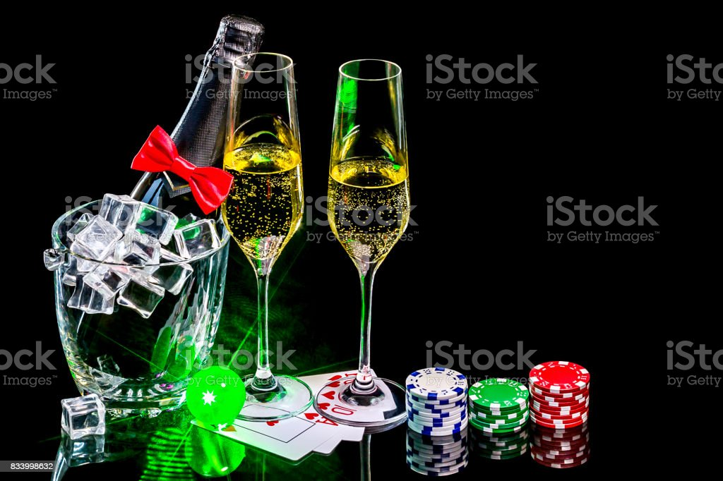 Bottle of champagne in an ice bucket with wineglasses and poker cards with chips stock photo
