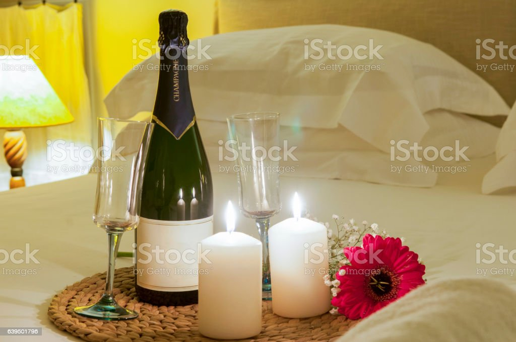bottle of champagne in bed stock photo