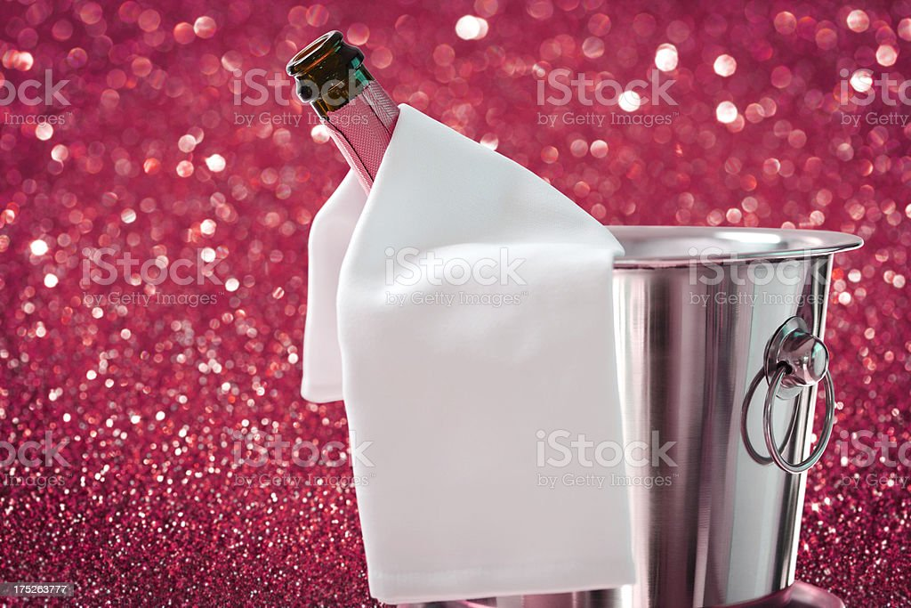 Bottle of Champagne in Ice Bucket against Defocused Background stock photo