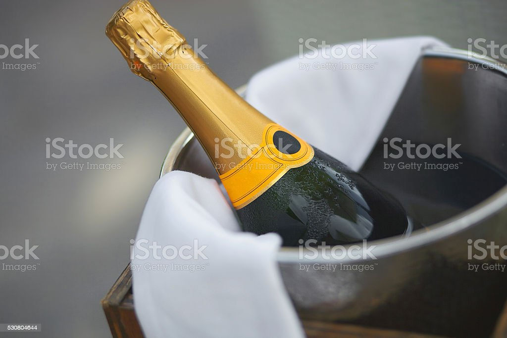 Bottle of champagne in ice bucket in restaurant. stock photo