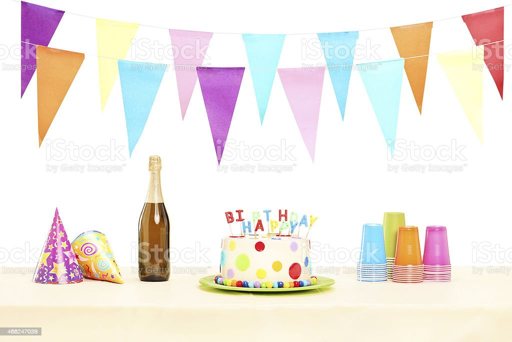 Bottle of champagne plastic glasses, party hats and birthday cake stock photo