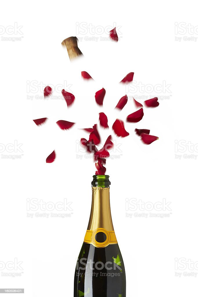 Bottle of champagne popping red rose petals with cork stock photo