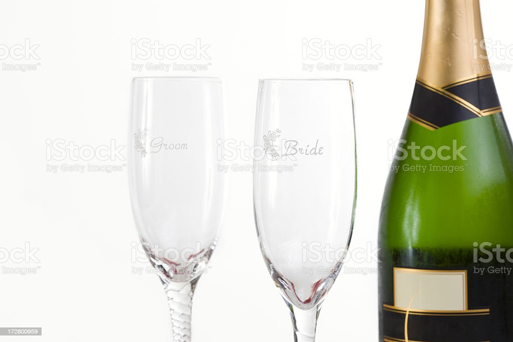 Bottle of Champagne With Bride and Groom Flutes on White stock photo