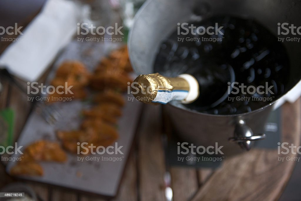 Bottle of champagne with food on a table royalty-free stock photo