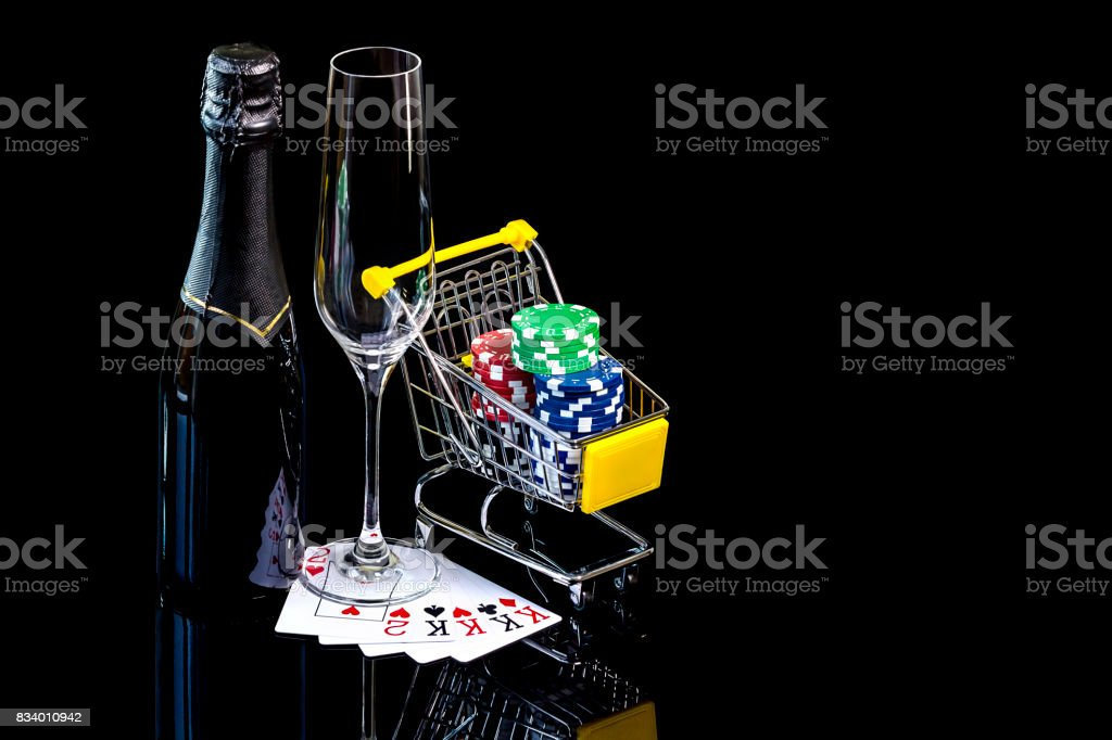 Bottle of champagne with wineglass and poker cards with chips stock photo