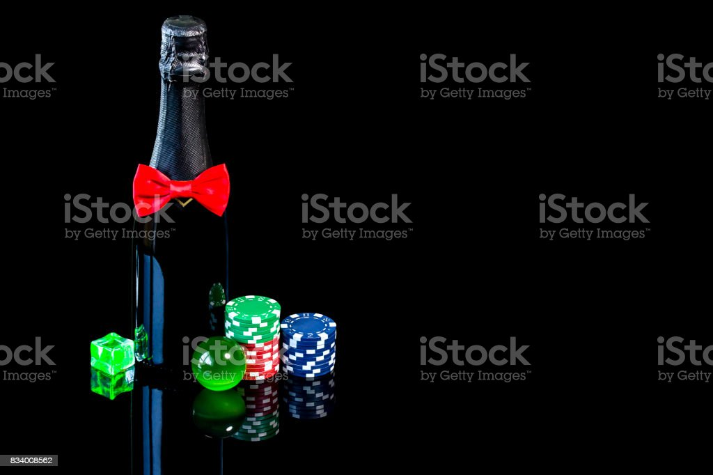 Bottle of champagne with wineglass and poker chips stock photo