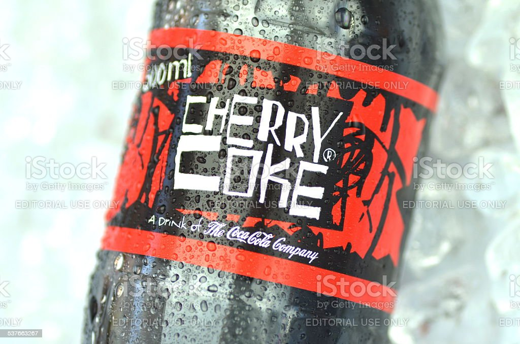 Bottle of Cherry Coke drink on ice cubes stock photo