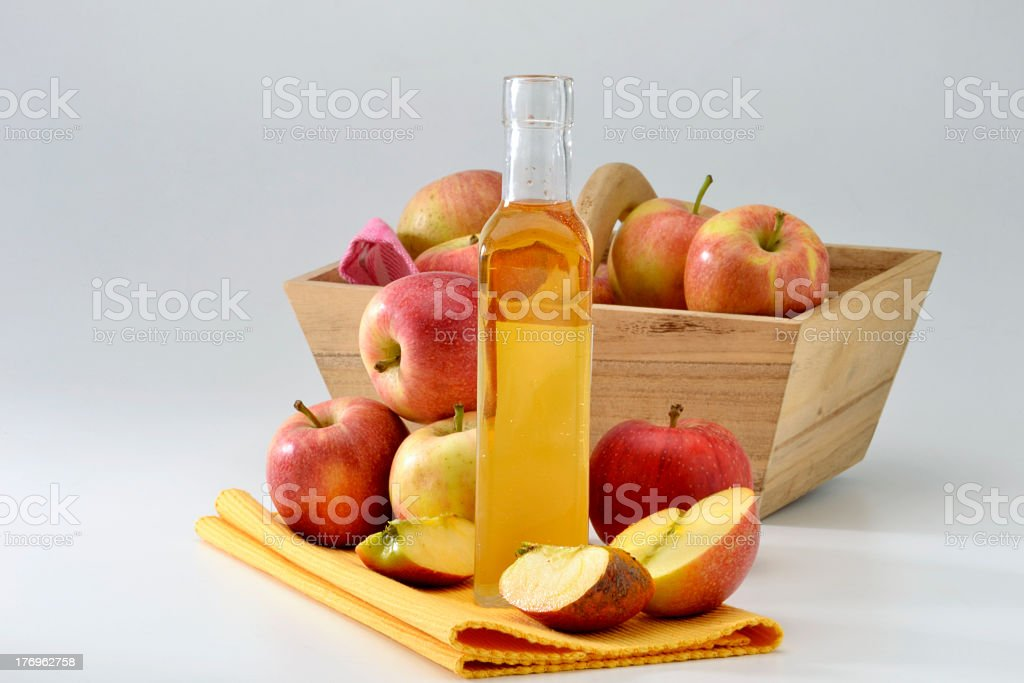 Bottle of cider vinegar next to apples and basket of apples royalty-free stock photo