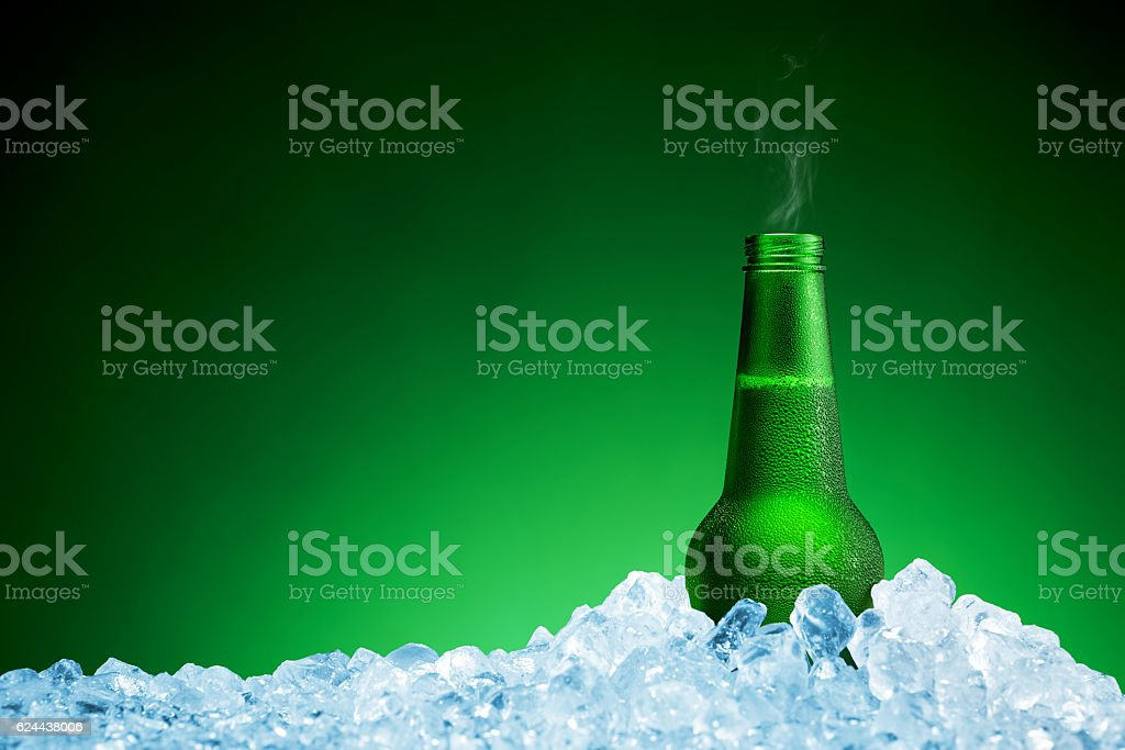 Bottle of cold beer in ice on green background stock photo