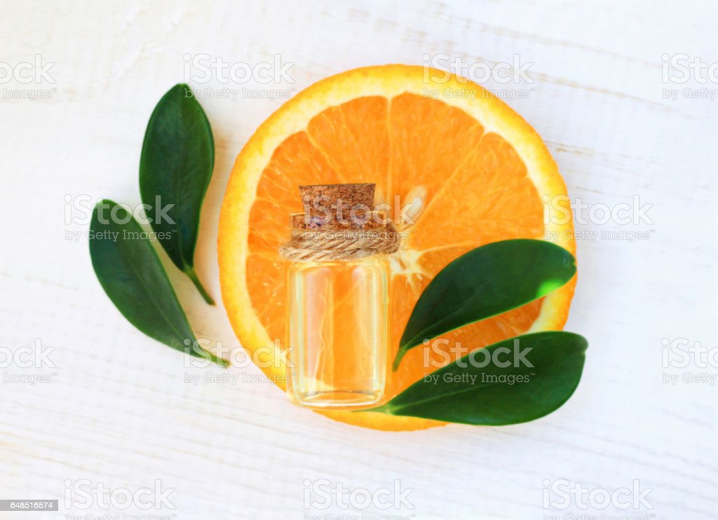 Bottle of essential aroma oil on orange slice stock photo