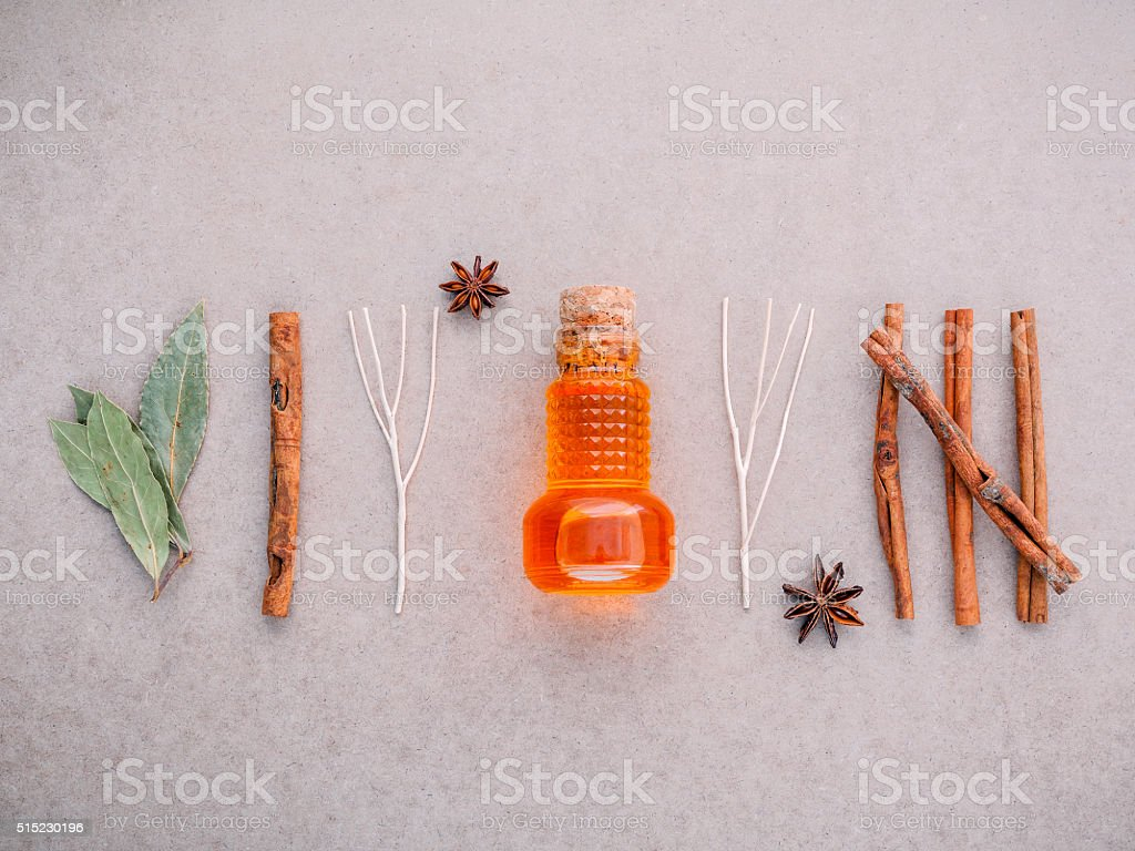 Bottle of essential oil with cinnamon stick . stock photo