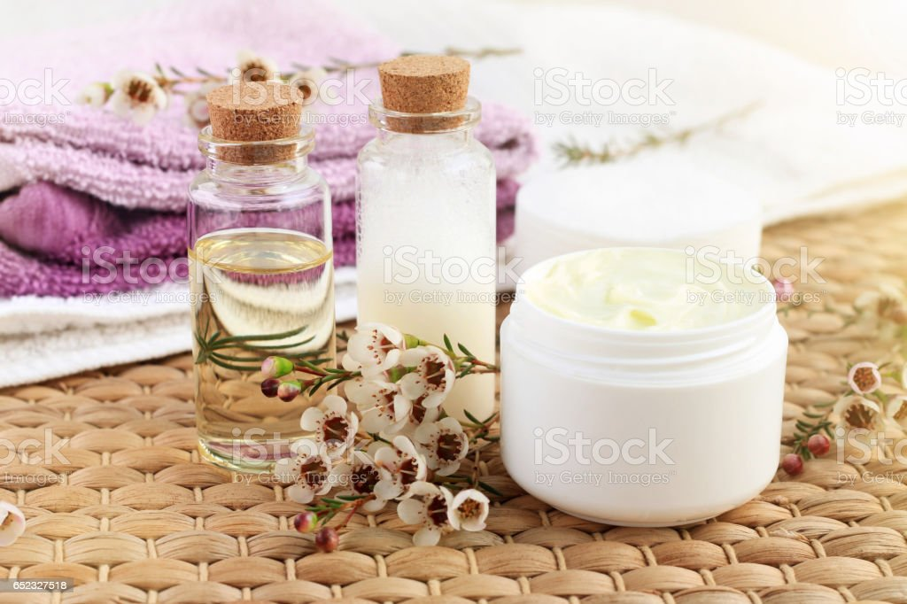 Bottle of essential oil with flowers, jar of facial moisturizer, towels, sunlight. stock photo