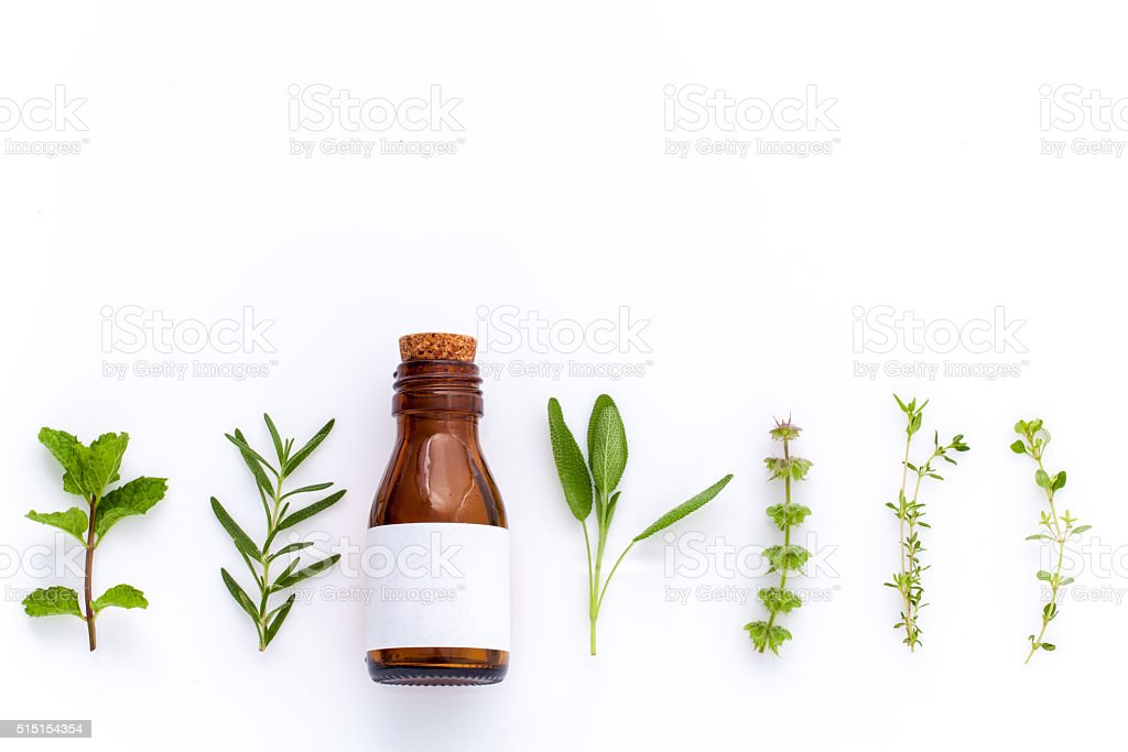 Bottle of essential oil with herb. stock photo