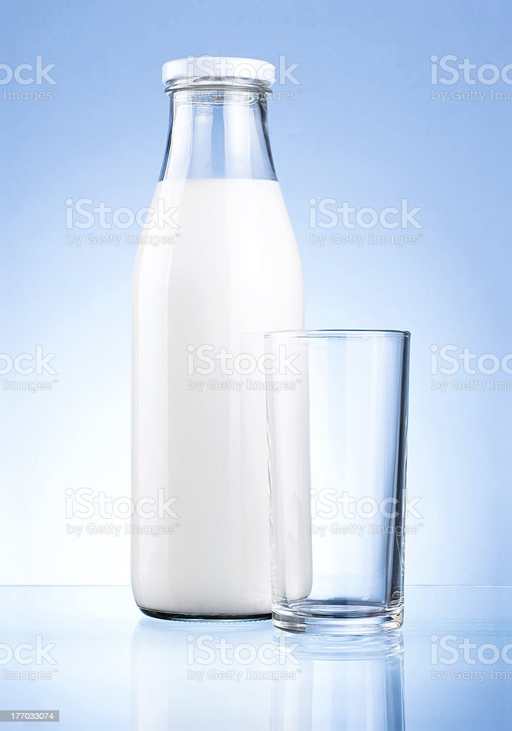 Bottle of fresh milk and blank glass on blue background royalty-free stock photo