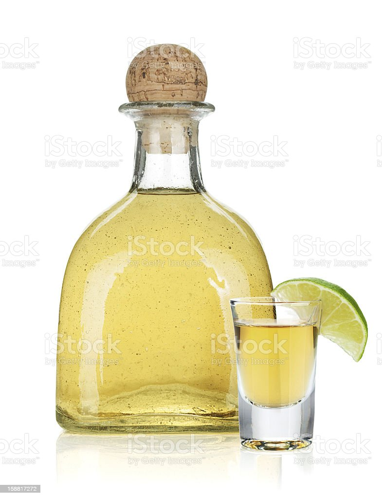 Bottle of gold tequila next to lime garnished glass stock photo
