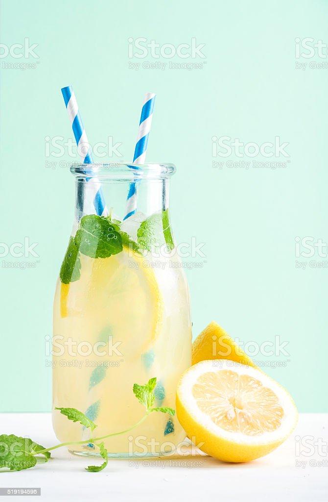 Bottle of homemade lemonade with mint, ice, lemons, paper straws stock photo