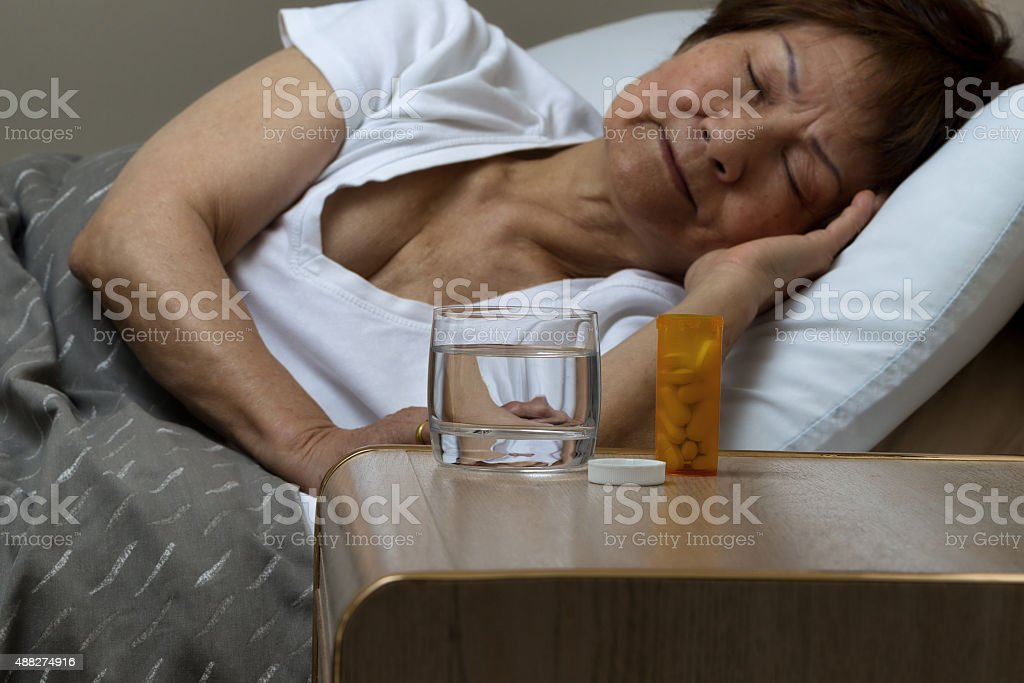 Bottle of medicine and water with senior woman sleeping stock photo