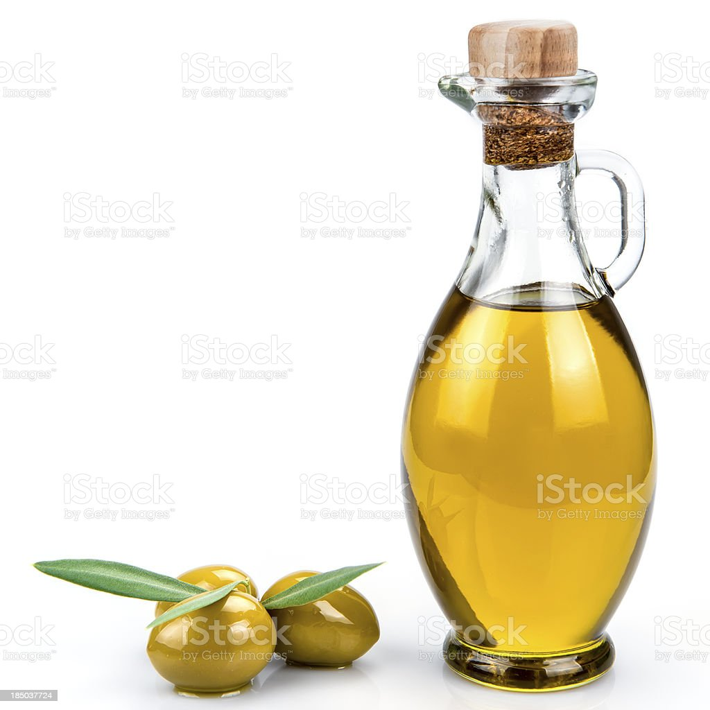 Bottle of olive oil next to large olives on white background stock photo
